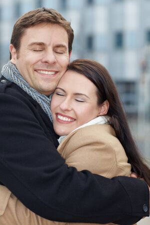 winter couple: Happy attractive couple in love embracing in winter