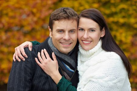 Happy man and smiling attractive woman in autumn photo