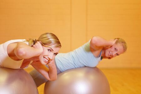 Two happy women exercising with gym ball in health club photo