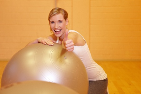 fit ball: Happy woman in fitness center holding her thumbs up
