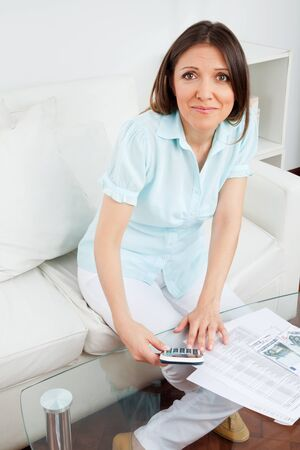 Woman with money and calculator in her living room Stock Photo - 12108717