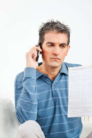 Man with cell phone and phone bill in living room Stock Photo - 12108731