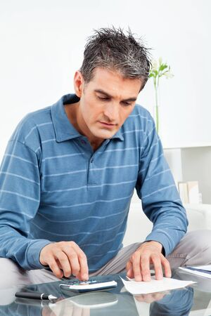 worries: Man with calculator and bills on living room table