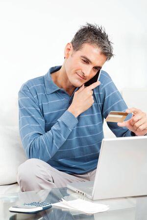 llamando: El hombre de compras en línea con tarjeta de crédito y teléfono celular