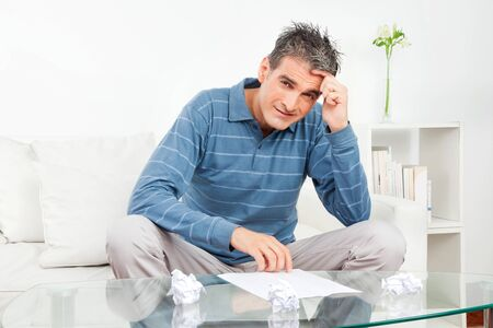Pensive man with some wadded paper balls on living room table Stock Photo - 12108714