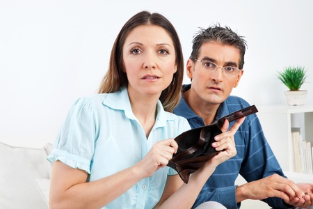 Elderly couple showing empty wallet in living room photo