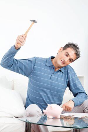 Angry senior man hitting piggy bank with hammer Stock Photo - 12108712