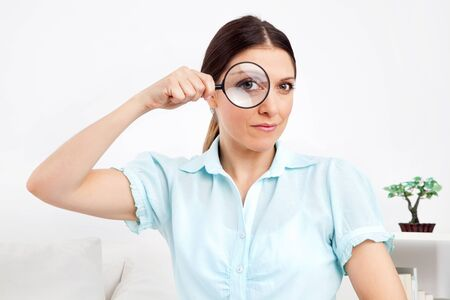 Elderly woman looking through magnifying glass with her eye photo