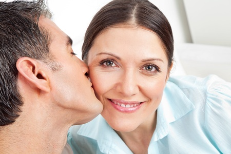 coziness: Elderly man kissing his smiling woman on the cheek