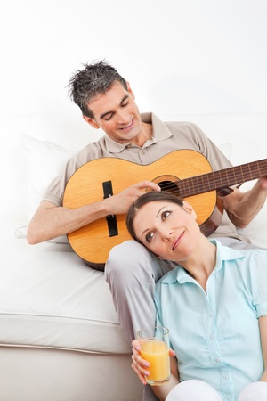 Happy man playing guitar for woman in living room photo