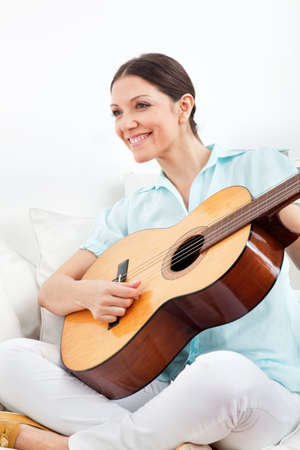 Elderly happy woman learning to play guitar photo