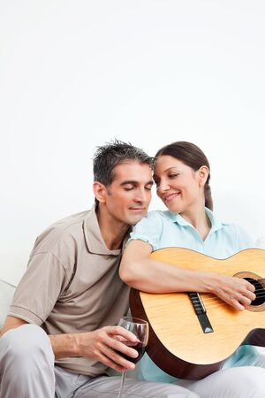 Man with wine and woman with guitar in living room photo
