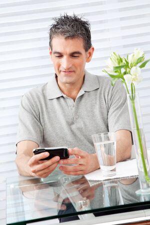 wlan: Elderly man looking at his smartphone in restaurant