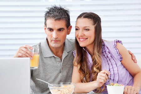 Elderly couple looking at laptop at breakfast table photo