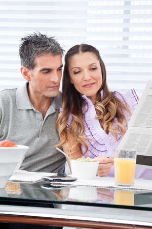 Couple reading newspaper in the morning at breakfast table photo
