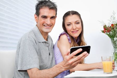 Man and woman using Social Networking with smartphone at breakfast photo