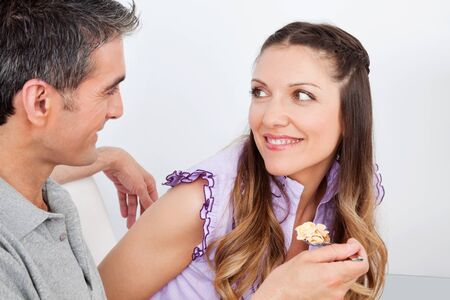 Man feeding smiling woman with spoon of cereal photo