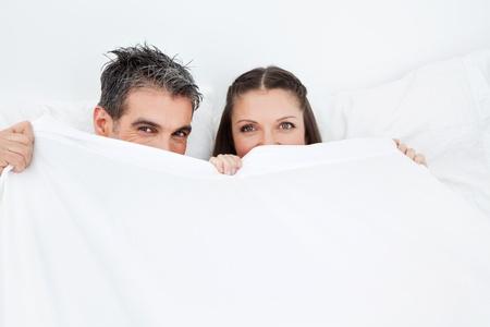 Pareja atrapada en la clandestinidad acto en la cama detr�s de las s�banas blancas Foto de archivo - 12108617