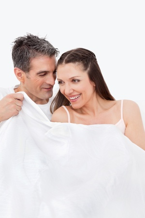 Happy senior couple talking in bed to each other Stock Photo - 12108618
