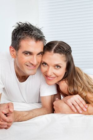 Married senior couple laying smiling in bed Stock Photo - 12108782