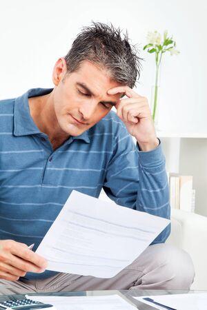 hombre preocupado: Hombre preocupado con las cuentas y la calculadora en la mesa en la sala de Foto de archivo