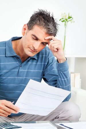 worried man: Worried man with bills and calculator at table in living room