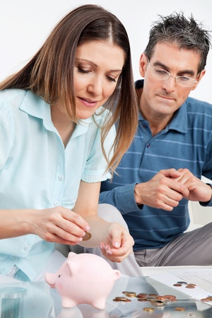 nursing allowance: Senior couple with money and piggy bank on table Stock Photo