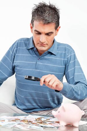 savings problems: Man with money and piggy bank looking through magnifying glass Stock Photo
