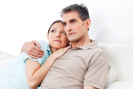 coziness: Pensive senior couple thinking on couch at home Stock Photo