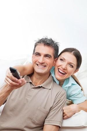 Happy couple watching TV with remote control at home photo
