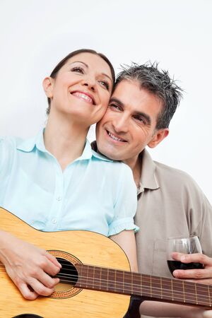 Happy woman playing guitar for smiling man photo