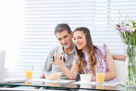 Happy couple with laptop and smartphone at breakfast table photo
