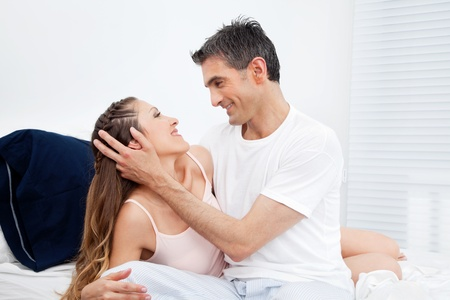 Happy married couple cuddling in their bed Stock Photo - 12108854
