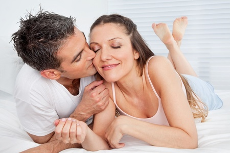 Senior man kissing happy woman in bed Stock Photo - 12108824