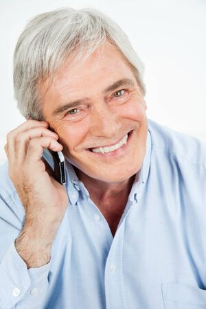 Happy senior man smiling while talking on smartphone photo