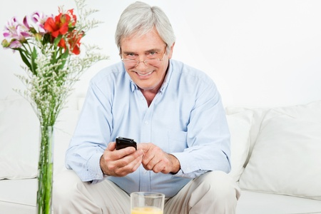 Happy senior man using a smartphone on the couch photo
