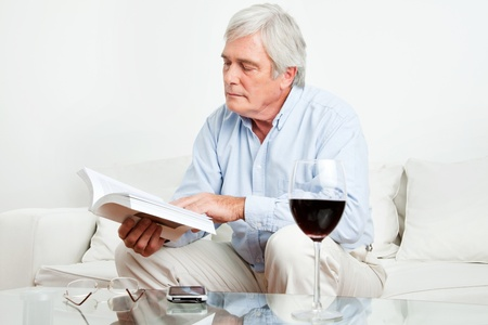 Senior man reading a book on the couch in the living room photo