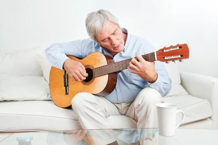 man playing guitar: Senior man at home learning to play guitar