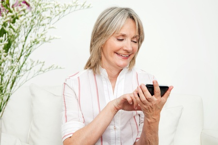 senior living: Senior woman playing an online game on smartphone Stock Photo