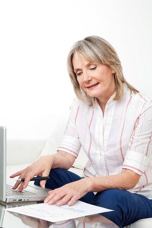 Happy senior woman working on laptop with stock prices photo