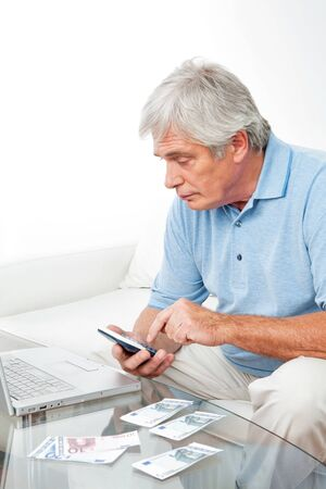 Senior man at home with calculator, laptop and Euro money photo