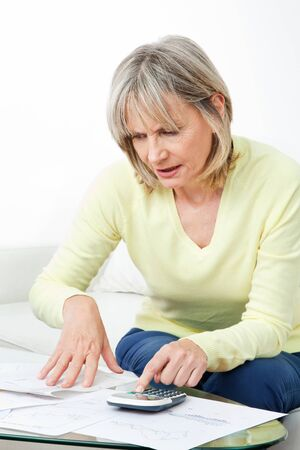 Senior woman checking pension approval certificate with calculator at home photo