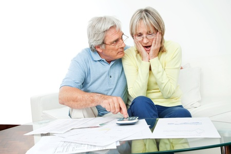 Worried senior couple sitting with bills and calculator at home photo