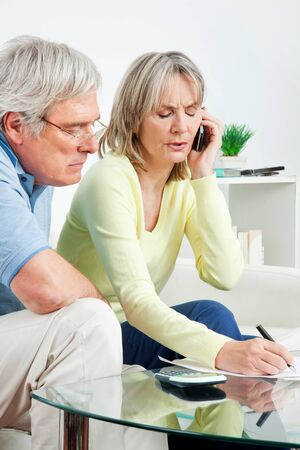 Senior couple with paperwork calling phone hotline at home photo