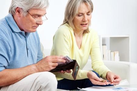 Anziano, coppia con portafoglio contando i soldi euro sul tavolo di casa