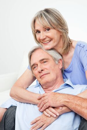 matchmaking: Two happy seniors embracing each other at home on couch Stock Photo