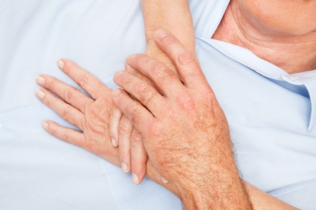 condolence: Two pair of senior hands touching each other gently