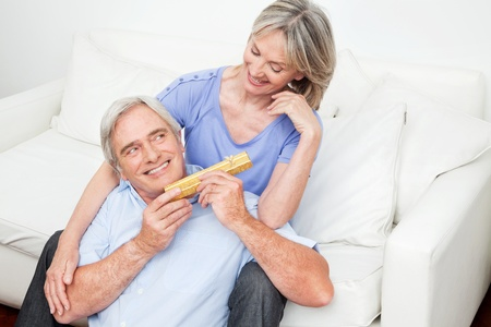 Senior giving his smiling woman a valentines day gift photo
