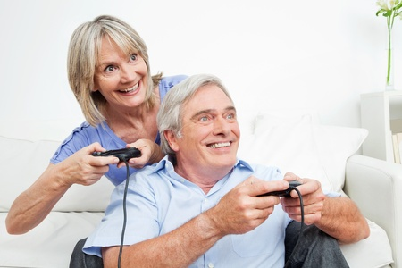 Happy senior couple playing video games at home with controller photo