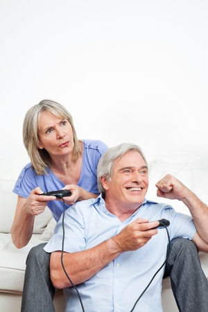 Two happy seniors playing video games at home photo